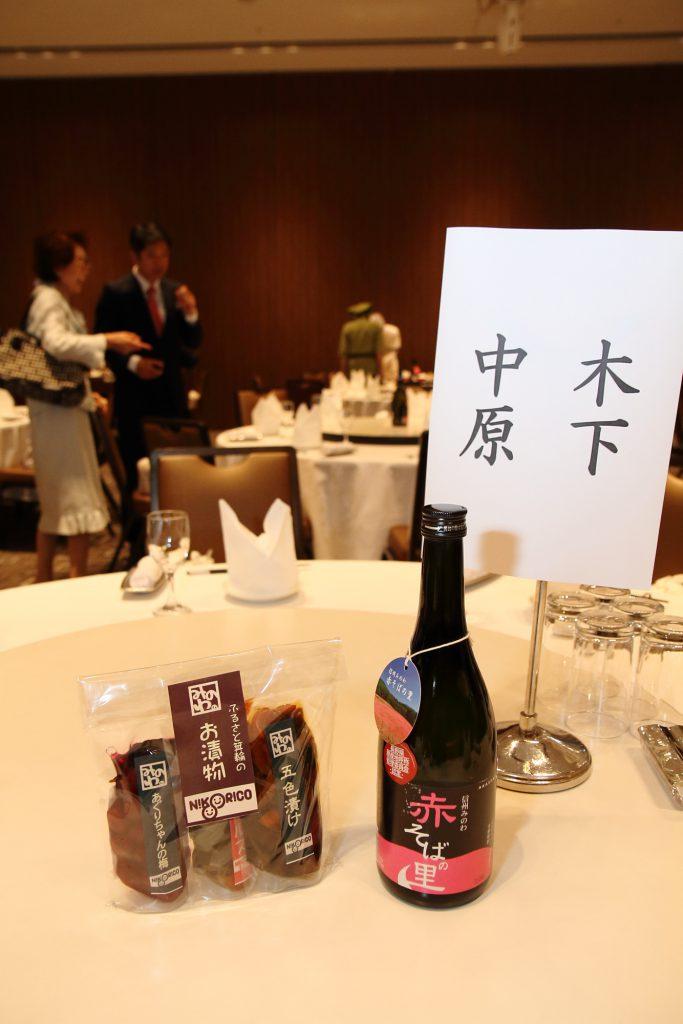 テーブルの上には、みのわ町より提供いただいたそば焼酎。横の漬け物セットは参加者全員に配られるお土産。