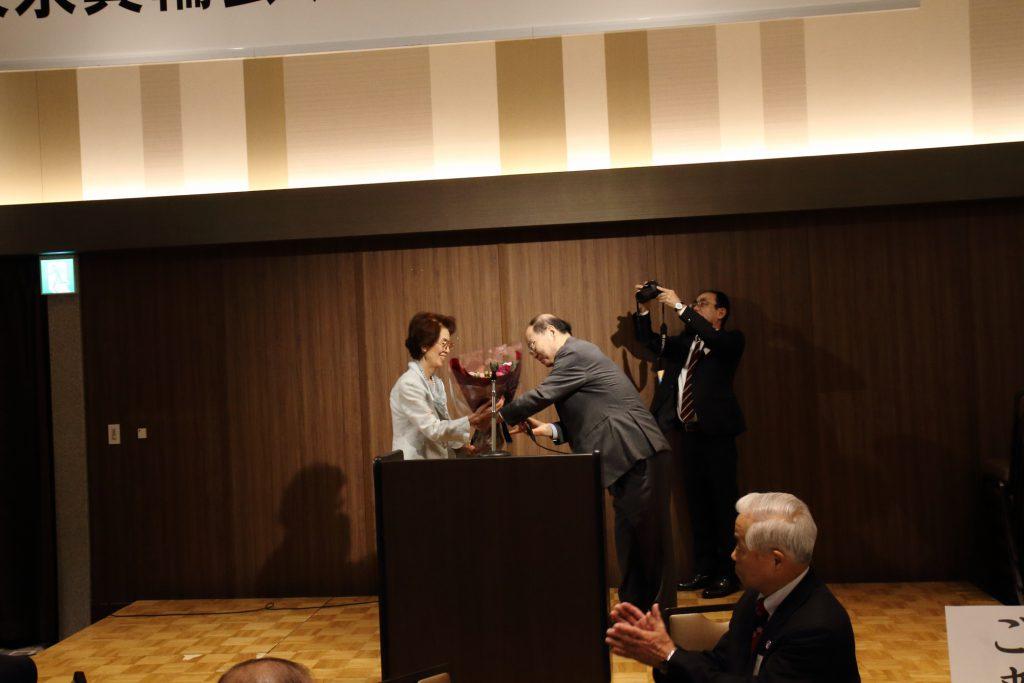 浦野東洋一新会長から、山口信子前会長へ感謝の花束贈呈。後ろで写真を撮っているのは、みのわ新聞の市川支社長。